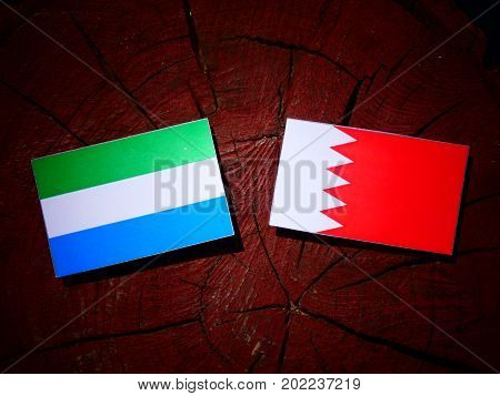 Sierra Leone Flag With Bahraini Flag On A Tree Stump Isolated
