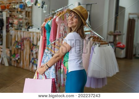 A close-up portrait of a smiling young woman on a store background. A satisfied female holding her stylish purchases in a clothing store. Shopping, consumerism, money concept. Copy space.