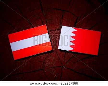 Austrian Flag With Bahraini Flag On A Tree Stump Isolated