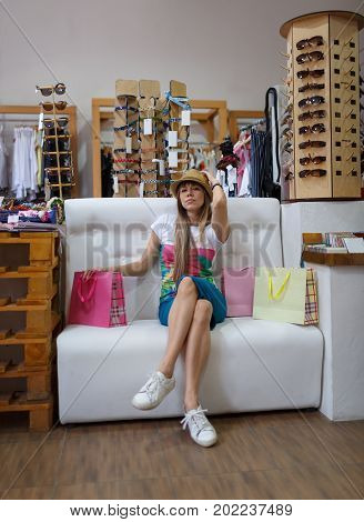 A full-length portrait of a sitting young woman on a clothing store background. A stylish female on sofa trying on a beautiful hat in a clothing store. Shopping, consumerism concept. Copy space.