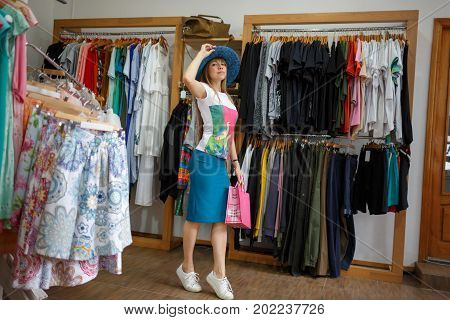 Shopping concept. A full-length portrait of a standing young woman on a clothing store background. A stylish female with a bright shopping bag trying on a beautiful hat in a clothing store. Copy space