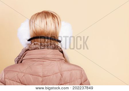 Woman In Winter Earmuffs And Jacket Back