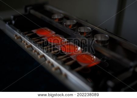 Close-up picture of a professional smelting gold machine in process. A bright red melting steel in little shaping forms on a blurred dark background. Metallurgical production of steel, bronze, metal.