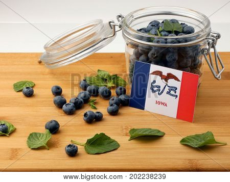 Iowa Flag On A Wooden Plank With Blueberries Isolated On White