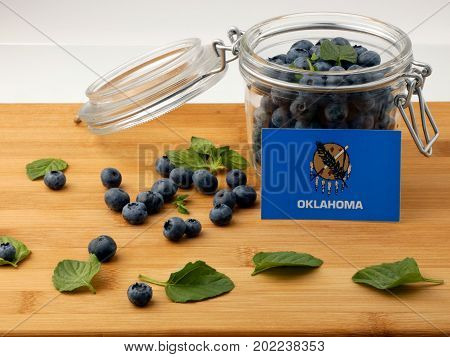 Oklahoma Flag On A Wooden Plank With Blueberries Isolated On White