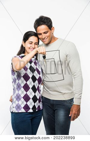 stock photo of Indian smart and young couple holding Key of new house or car  and standing over white background. Cheerful asian husband and wife with house / car keys