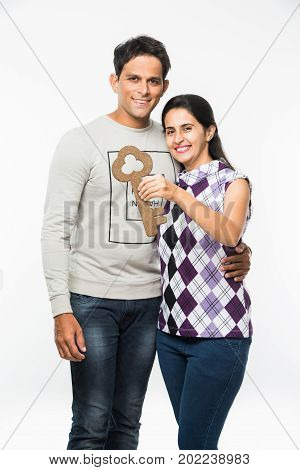 stock photo of Indian smart and young couple holding dummy big Key of house or car  and standing over white background. Cheerful asian husband and wife with house / car keys