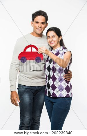 stock photo showing attractive indian young couple holding dummy car made up of cardboard, indian people and car buying concept