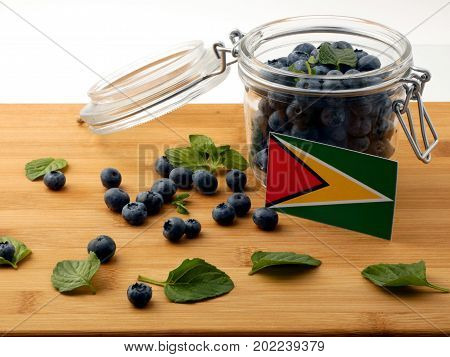Guyana Flag On A Wooden Plank With Blueberries Isolated On White