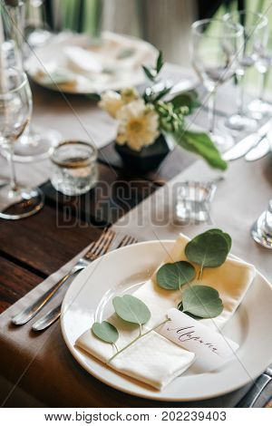 Table place card with the guest's name on the plate. Beautiful table set for any holiday event party or wedding.