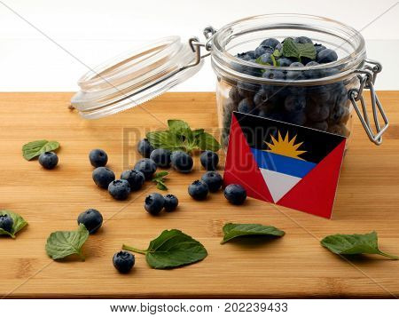 Antigua And Barbuda Flag On A Wooden Plank With Blueberries Isolated On White