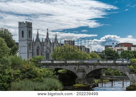Galway Ireland - August 5 2017: Saint Vincents convent of Mercy behind Salmon Weir Bridge under blue sky with white clouds. Corrib River and green trees on its shore.