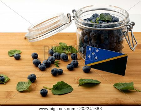 Solomon Islands Flag On A Wooden Plank With Blueberries Isolated On White