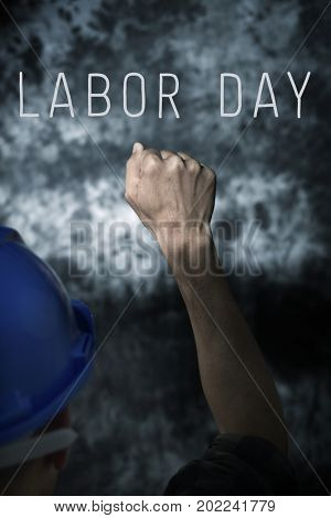 closeup of a young caucasian man seen from behind wearing a blue hard hat and with his fist raised to the air, against a gradient gray background and the text labor day