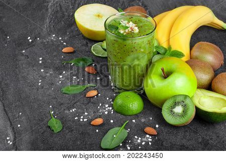 An organic composition of a fresh kiwi smoothie with grated almond and tropical fruits on a dark gray stones background. A branch of yellow bananas, cut apple, avocado and kiwi on a table.