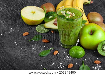 A colorful composition of an organic kiwi smoothie with grated almond and tropical fruits on a dark stones background. Whole and cut apples, kiwi, avocado and a branch of yellow bananas on a table.