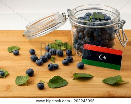 Libyan Flag On A Wooden Plank With Blueberries Isolated On White