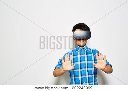 Young man in checked shirt having fun while experiencing virtual reality with help of VR headset, studio shot