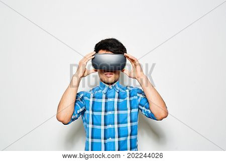 Waist-up portrait of young man wearing blue checked shirt using VR headset while standing against white background