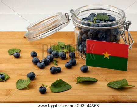 Burkina Faso Flag On A Wooden Plank With Blueberries Isolated On White