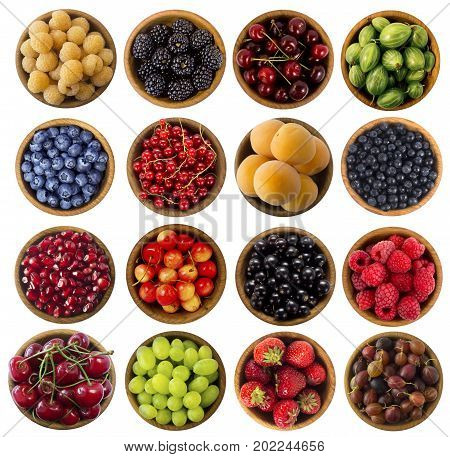 Collage of different fruits and berries isolated on white. Raspberries blackberries cherries gooseberries blueberries currants apricots blueberries grapes strawberries gooseberries and pomegranate. Top view