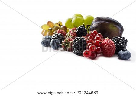 Various fresh summer berries on white background. Ripe raspberries blackberries blueberries red currants grapes and plums mint. Berries with copy space for text. Background berries.