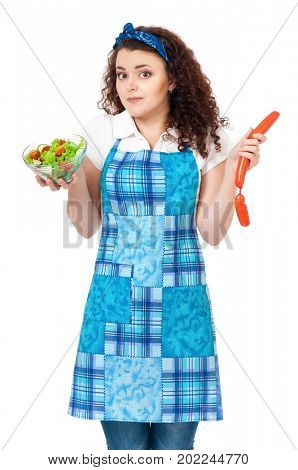 Beautiful young woman choosing between fresh salad and sausages