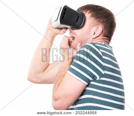 Young man with a frightened pose with virtual reality goggles watching movies or playing video games, isolated on white background. Man is looking scared. People experiencing 3D gadget technology.