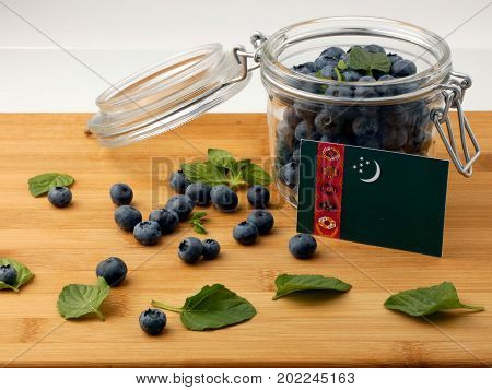 Turkmenistan Flag On A Wooden Plank With Blueberries Isolated On White