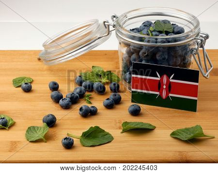 Kenyan Flag On A Wooden Plank With Blueberries Isolated On White