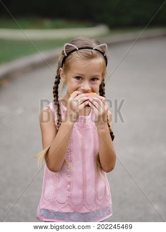 A close-up portrait of a beautiful little girl with hamburger in her hands on a blurred street background. An attractive girl with pigtails is eating a sandwich. Unhealthy food.