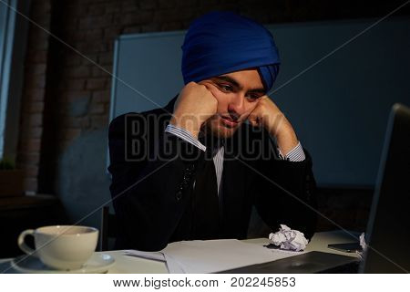 Tired businessman in suit and turban looking at laptop display late at night