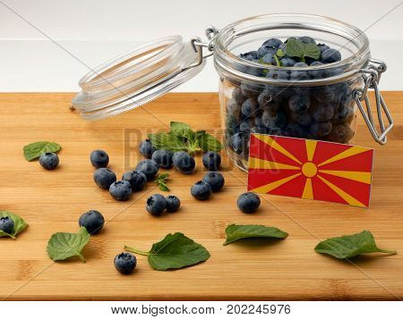 Macedonian Flag On A Wooden Plank With Blueberries Isolated On White