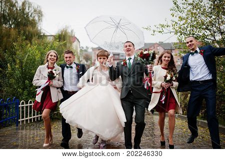 Wedding Couple And Groomsmen With Bridesmaids Walking On A Rainy Day With An Umbrella.