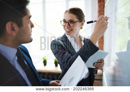Happy professionals pointing out ideas and main business points on whiteboard