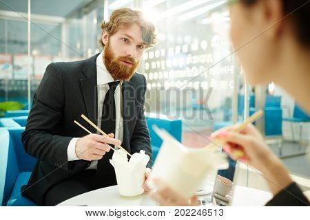 Young colleagues with chopsticks and chinese noodles talking at lunch break in office