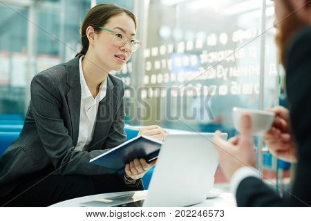 Young woman with notebook talking to colleague at meeting