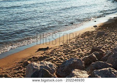 Panorama of deserted seashore illuminated with evening sunbeams: blue water surface with small waves, soft sand and heavy rubble stones