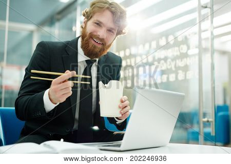 Young office worker with chinese food eating at workplace