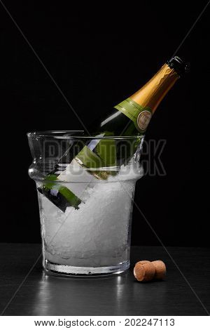 A close-up picture of a bottle of chilled champagne in a transparent bucket with crushed ice on a saturated black background. A wooden cork from a bottle of alcoholic drink on a bar counter.
