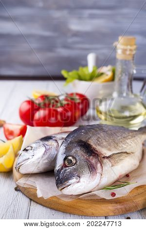 Fresh raw fish and food ingredients and tomato on stone table