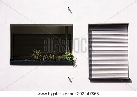 A new and modern balcony of an apartment of a multi-family house with balcony flowers and a window with blinds.