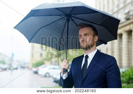 Businessman in formalwear standing under umbrella in the rain