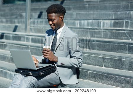Jobless man with drink and laptop searching for vacancies in the net