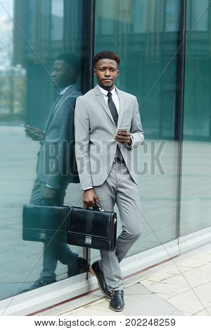 Well-dressed man with briefcase standing by glassy wall of modern office-building