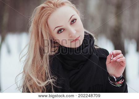Woman winter snow nature portrait in black coat.