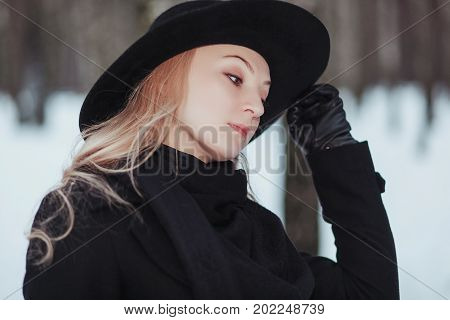 Woman winter snow nature portrait in black coat and hat.