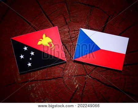 Papua New Guinea Flag With Czech Flag On A Tree Stump Isolated