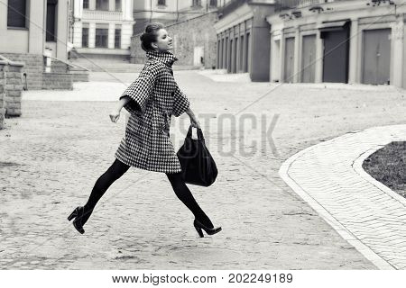 fashion and people concept - happy young woman or teenage girl running and jumping high on city street.