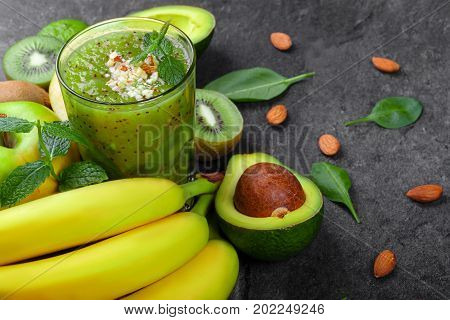 A view from above of a refreshing and exotic smoothie full of vitamins and kiwis on a gray table background. A composition from ripe bananas, organic avocado, mint, cut kiwi and apple on a desk.